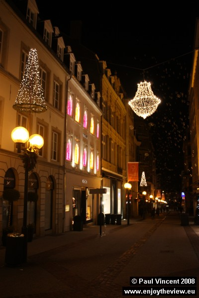 Christmas lights hang in this quiet street.