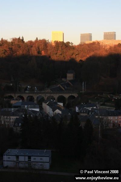 The tall blocks of the Kirchberg glisten in the sun as darkness falls on the Alzette valley.
