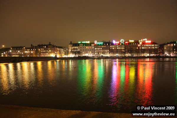 By night, the roof-top advertising provides a colourful reflection in lake Sortedams.
