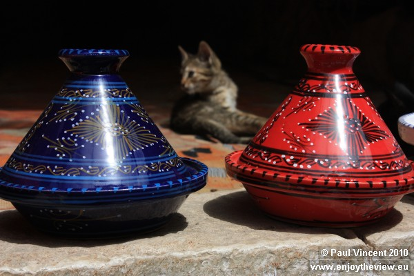 Souvenirs for sale, kitten playing behind.