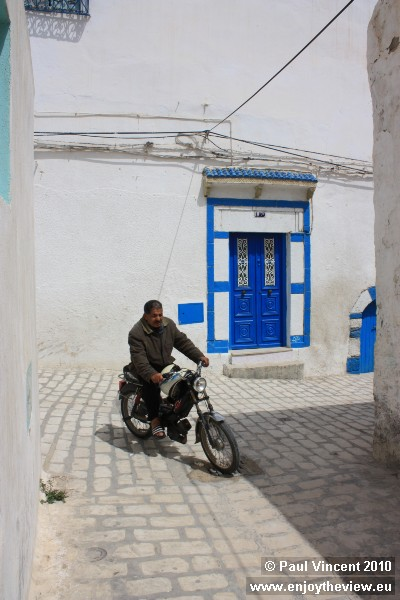 A motorcyclist navigates the narrow cobbled streets of this old town.