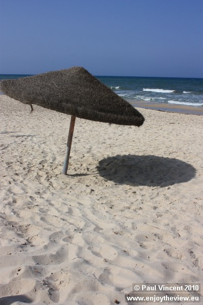 An umbrella offers little shade from the afternoon sun.