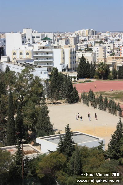 Teenagers play on this sandy football field.