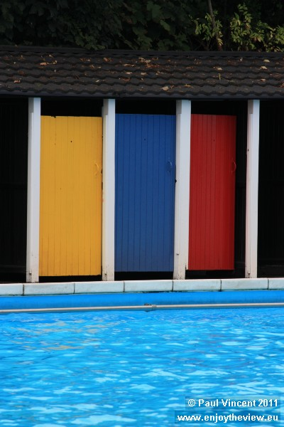 Brightly-painted changing cubicles line each side of the pool.
