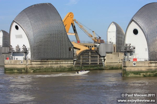 The Thames Barrier dwarfs a speedboat travelling through the structure.