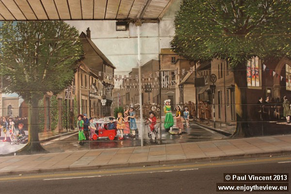 Depiction of a 1953 coronation street party on Pennyfarthing Street.