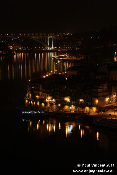 City lights reflect in the winding Douro river, viewed up to the Arrábida bridge.