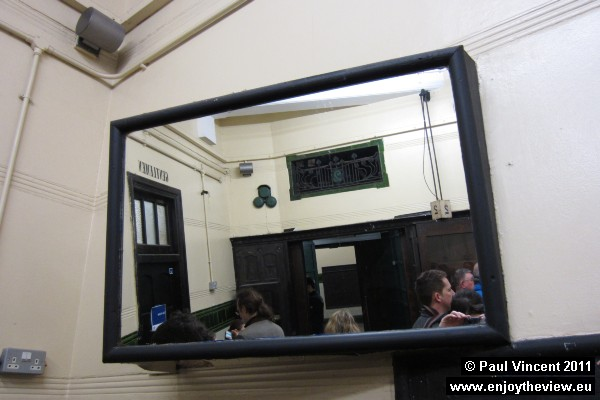 A mirror in the corner of the hallway, to give commuters a better view of both lifts from afar.